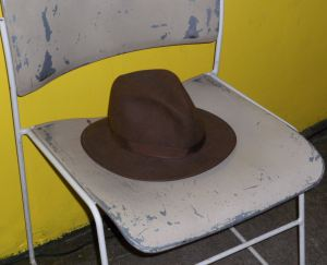 To the side of the stage, a battered chair sat with a brown fedora on the seat. This was the designated place of honor for AJ's hat.